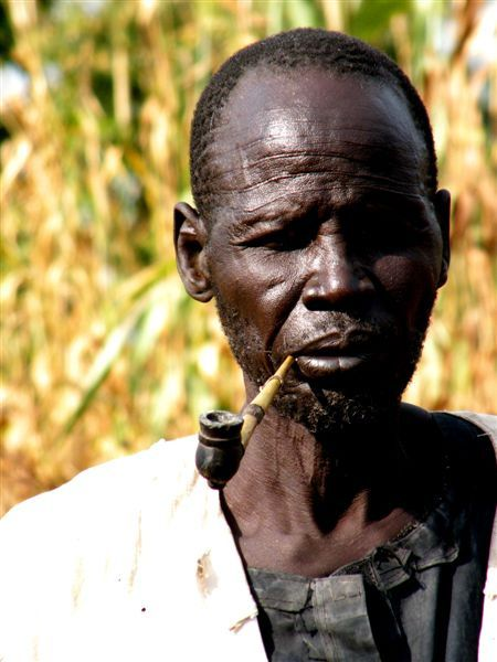 Sudanese elderly man smoking pipe