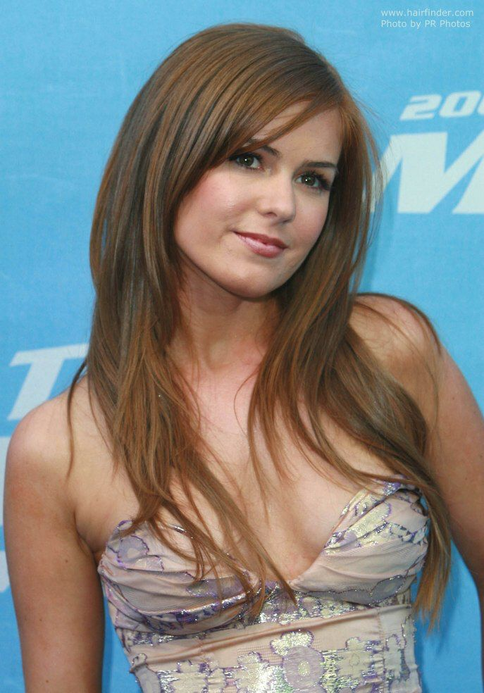 The long, reddish blonde hair was cut in big layers starting below the chin and the sideway bangs were tapered in a steep angle. The ends were strongly textured and fell in a soft fringy veil almost to Isla's waist. To style the hair is first blow dried for maximum volume and then smoothed and straightened with a flat iron. Shine spray keeps it all together and gives a sleek appearance. Isla Fisher's hair with tapered bangs Isla Fisher's straight reddish blonde hair Long hairstyle with side