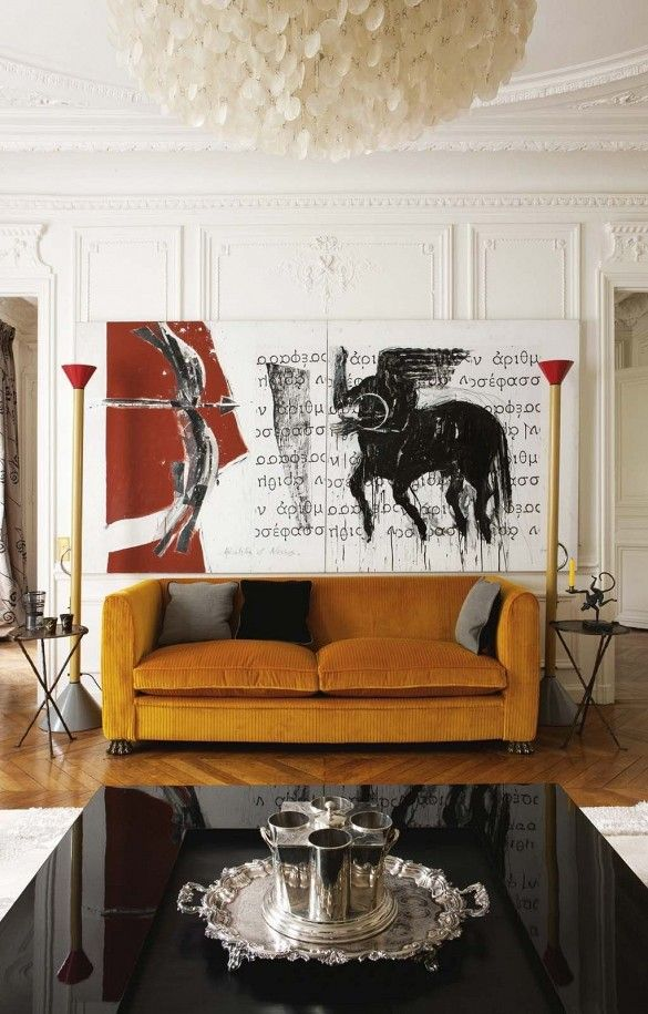 A modern orange sofa and contemporary art in a traditional room with moulding.