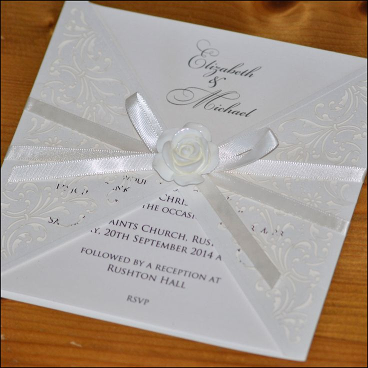 Laser cut wedding invitation finished with satin ribbon bow and resin rose.
