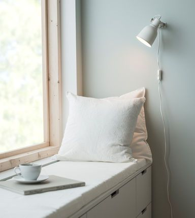 Window seating in a bedroom using a cushion, wall lamp and DIY mattress pad