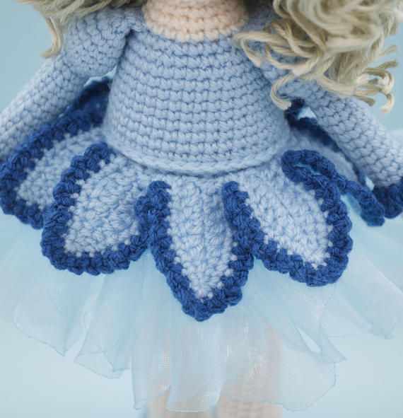 This is a finished handmade amigurumi crochet doll of a beautiful Bluebell flower doll. She wears a beautiful pale blue organza skirt topped with crochet petals made to look like a Bluebell flower. On her head of curls is a removable floral hat. Her shoes were made to match her