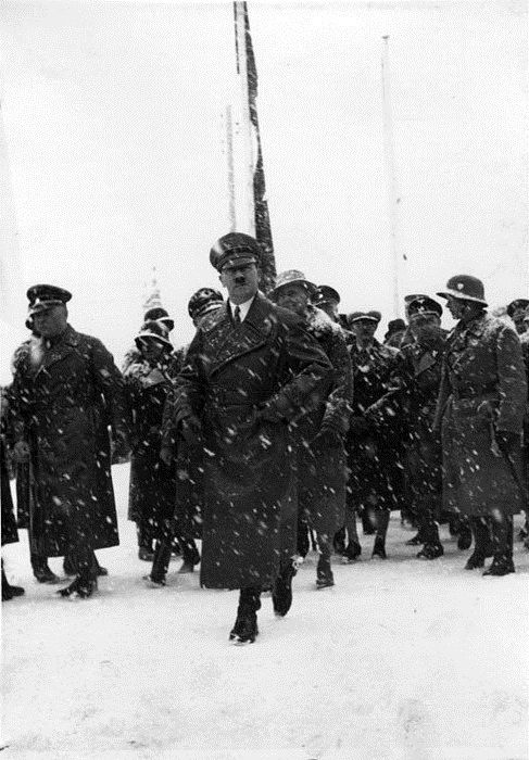 Hitler accompanied by his Leibstandarte SS Guardsmen and other government officials tread through the thick snow to attend a state function while a December blizzard falls upon the Reich.