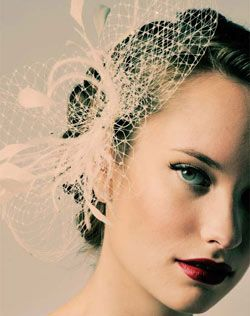 Birdcage veil, but doesn't cover the face, throw in a few white ostrich feathers.