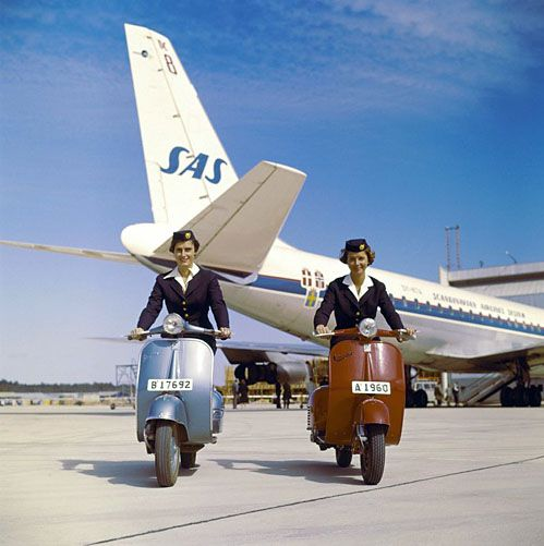 Stewardesses commuting on a Vespa, not a plane.