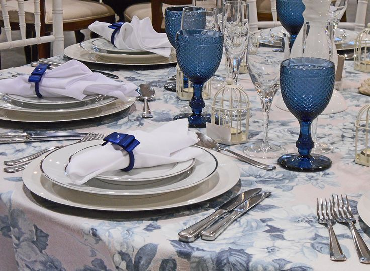 Tolha Azul Chá Floral, cadeiras Tiffany Branca, taças Bico de Jaca Azul, talheres Ópera.