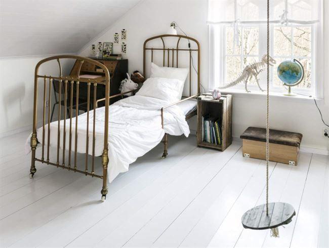 Charmigt inrett för barn med en vacker gammal järnsäng. Sänglampa från Ikea. Dinosaurie från Teknikmagasinet. Rund gunga från Biltema.