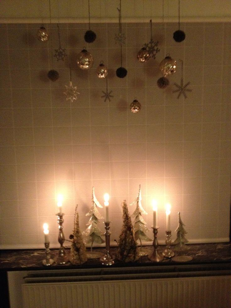 Diverse ophæng (uld pomponer, glaskugler, stjerner) over lysestager. Lysene får ophængene til at snore. / Ornaments and candles. The candles make the ornaments spin.