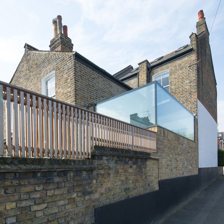 A glass box peeps over a brick wall at this Victorian property in east London, designed by local architecture practice Studio 304.