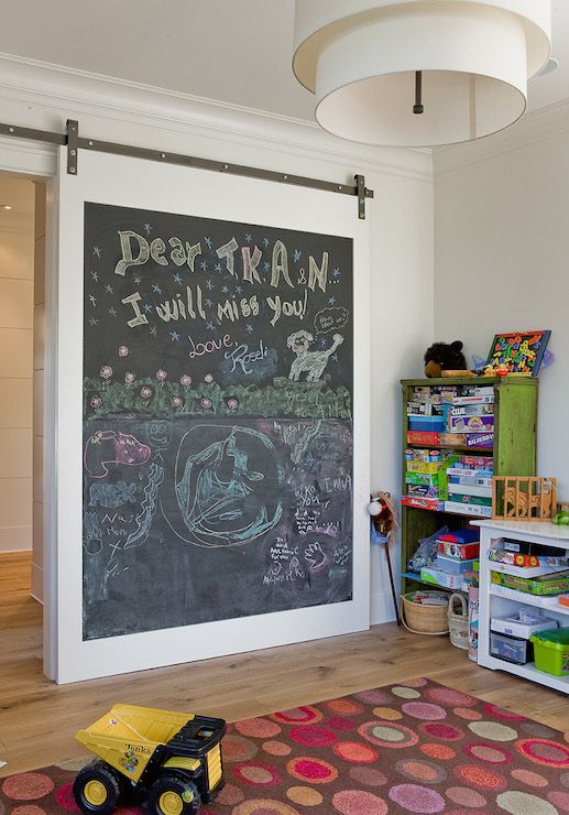 A chalkboard barn door on rails slides open to reveal playroom filled with distressed green bookcases stacked on top of each other beside a low white bookcase doubling as desk alongside a multi-color rug illuminated by a tiered drum chandelier.