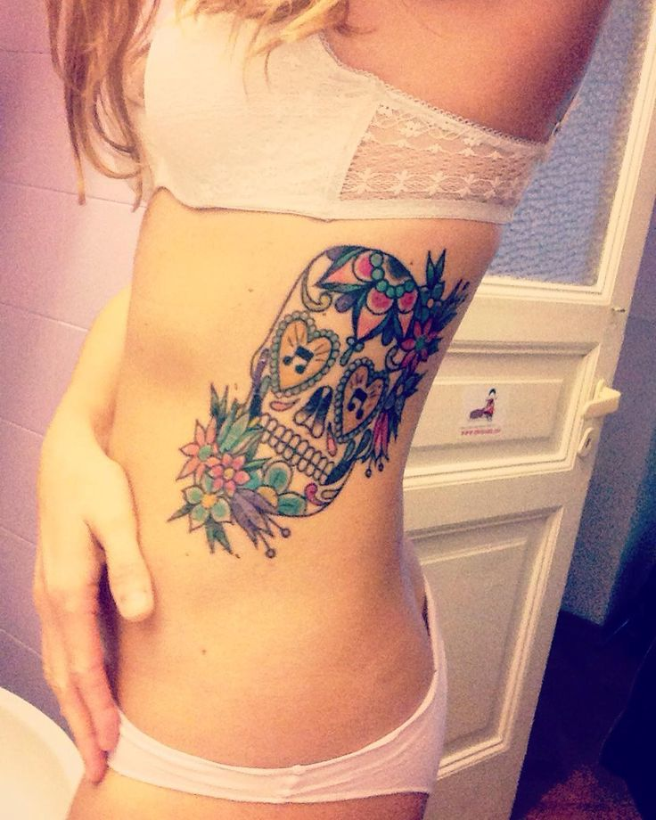 Sugar skull tattoo on woman's ribs with music and a lot of other symbols
