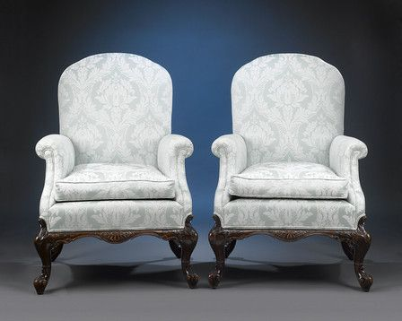 This classic and highly desirable pair of George II-style armchairs is crafted of luxurious Cuban mahogany. Their large, yet elegant design is bolstered by beautifully upholstered arms, seats and backs, and fully carved cabriole legs reminiscent of superior Georgian design. Distinctive pairs of chairs, exhibiting such grandiose size, excellent condition and high-caliber craftsmanship, are quite extraordinary finds on today's market and command a great deal of attention among connoisseurs…