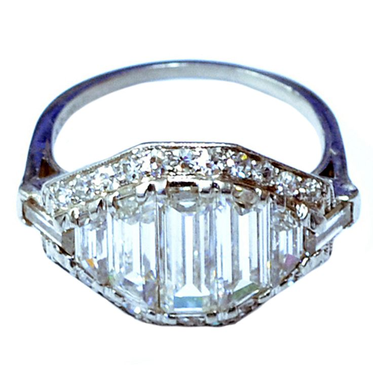 Art Deco Baguette Cut Diamond Ring  America  Circa 1920  An Art Deco baguette cut diamond ring, mounted in platinum. Having tapered baguettes to the center, framed by a row of brilliant cut diamonds on each side.  Price