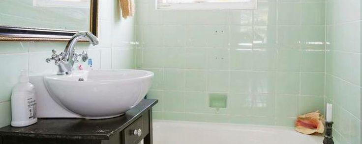 Husets tre badeværelser er blevet shinet op. Badet her i overetagen har de oprindelige fliser, terrazzogulv og badekar. Vask og toilet er nyt og udstyret med antikt bord, emaljespand, lampet og spejl. Foto: Jan Ove Kristensen
