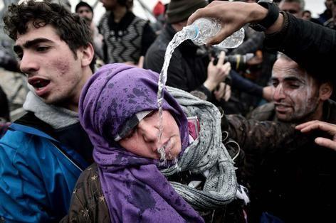 Een migrant gooit water in het gezicht van een vrouw die flauwviel toen ze haar kind was kwijtgeraakt in de menigte. De politie had traangas gebruikt toen de vluchtelingen demonstreerden bij de Grieks-Macedonische grensovergang op 29 februari.
