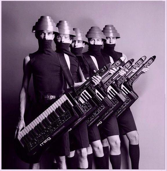 """Devo - American New Wave band formed in 1972 consisting of members from Kent and Akron, Ohio. The classic line-up of the band includes two sets of brothers, the Mothersbaughs (Mark and Bob) and the Casales (Gerald and Bob), along with Alan Myers. The band had a No. 14 Billboard chart hit in 1980 with the single """"Whip It"""", and has maintained a cult following throughout its existence."""