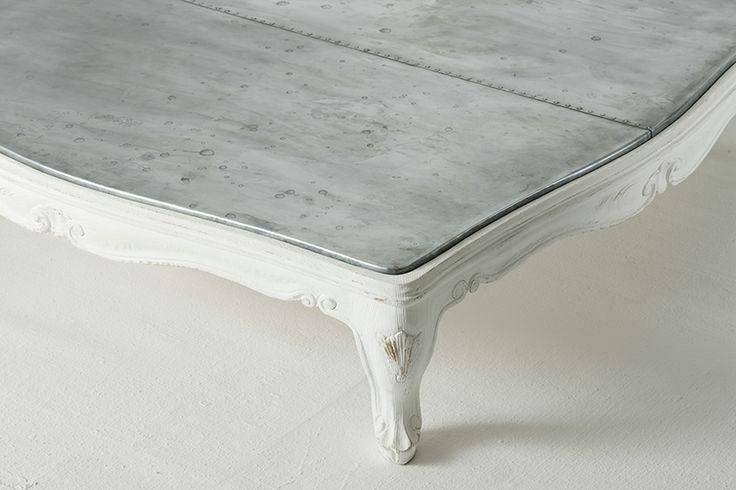 Tavolino basso con piano rivestito in zinco anticato e saldature a vista.