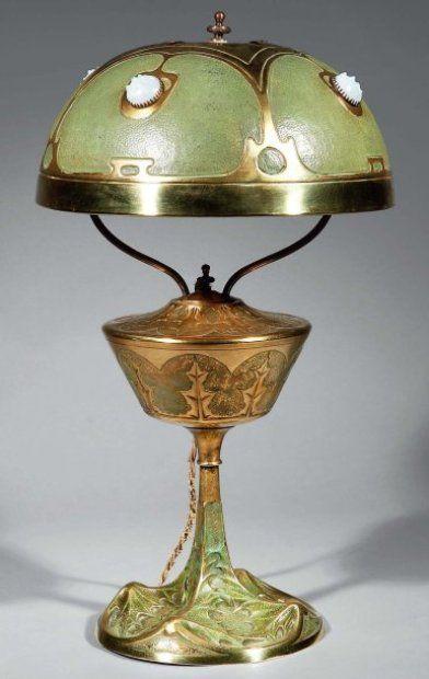 ART NOUVEAU - George LELEU, XXe siècle  Lampe chardon en bronze à patine verte et dorée, reposant sur un piédouche à décor végétal. Abat-jour semi-sphérique en laiton repoussé et ciselé de feuilles de chardons et à cabochons en opaline. Signé sur le pied. Vers 1900. Haut. : 46 cm