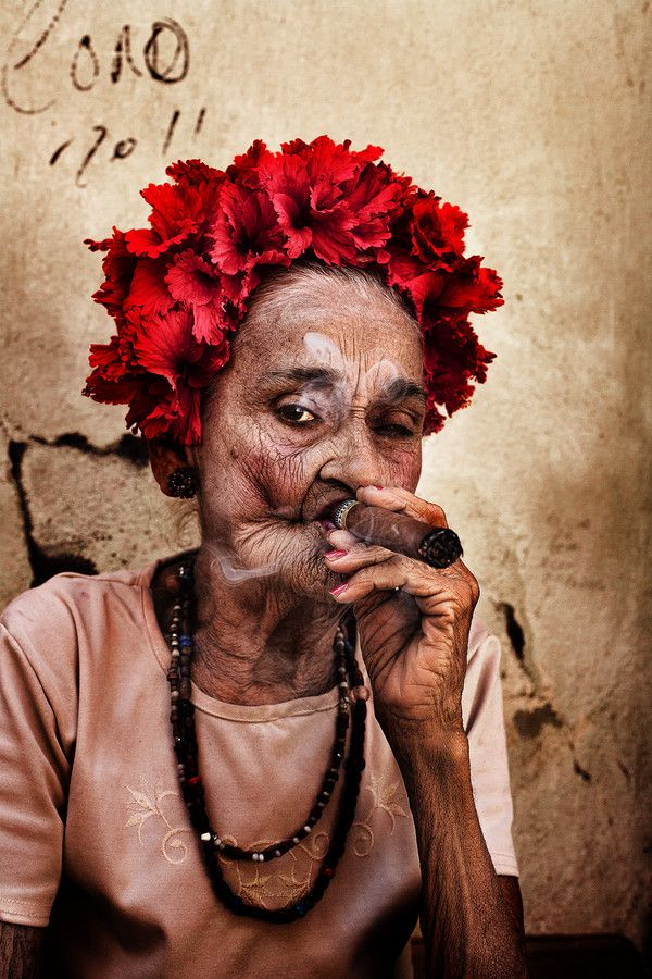 Cuban woman with bright floral head dress smoking a cigar, a snapshot of life in Cuba.