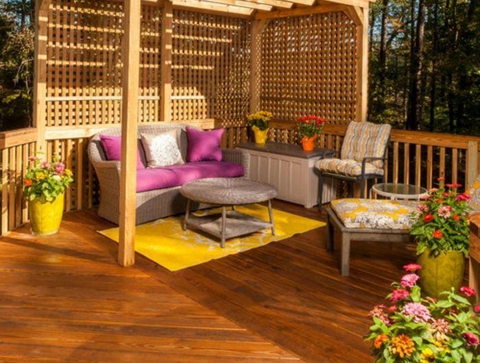 terrasse surélevée, tapis jaune, table basse ronde, pot à fleur jaune, coussins rose, auvent en bois