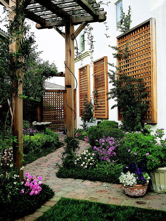 A narrow yard gains depth and interest with trellises, pergola, pavers and lush garden all set on an angle.: