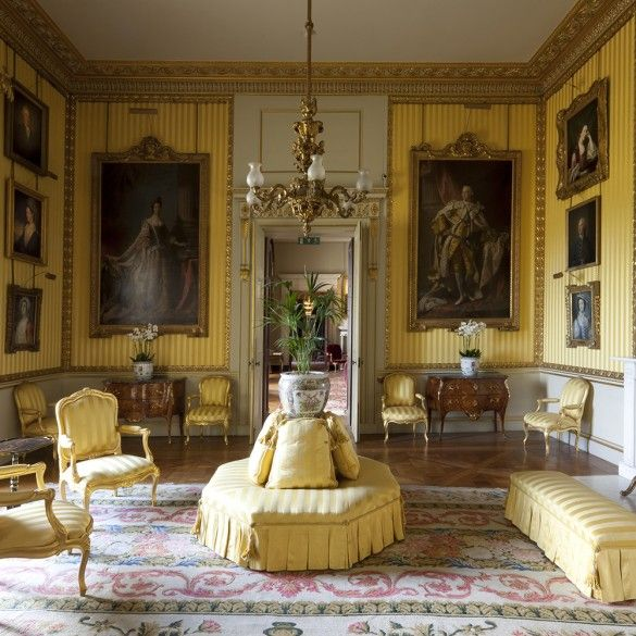state portraits of George III and Queen Charlotte flank entry of yellow drawing room of Duke of Richmonds home Goodwood House since 17th c.