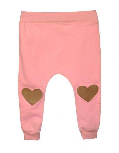 Lekkie spodnie dresowe z obniżonym stanem w kolorze różowym. Na kolanach ozdobne łatki w kształcie serca wykonane z ekoskóry w kolorze nude.