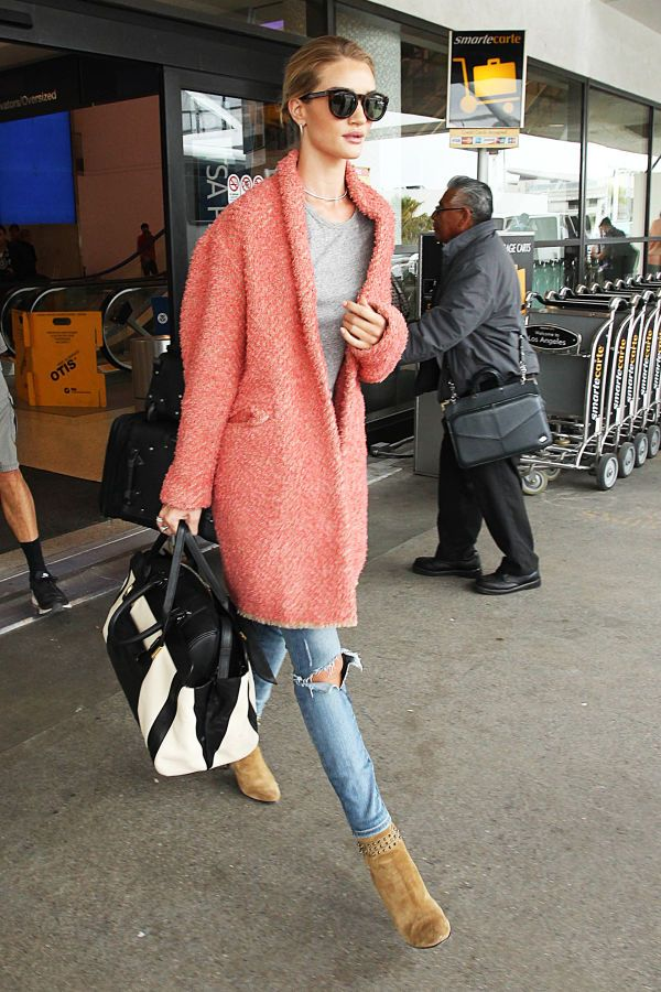 Rosie Huntington-Whiteley wears a nubby cardigan coat,  a grey tee, distressed denim, and suede booties to the airport.