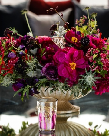 Colorful glasses with tea light candles surround this gilded footed compote of bold flowers