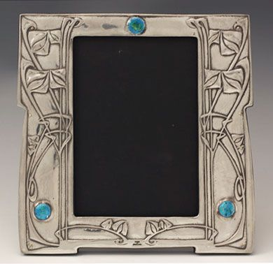 Archibald Knox (1864-1933) - For Liberty & Co. Picture Frame. Polished Pewter and Enamel with Wood Back. England. Circa 1905. 18cm x 18cm.