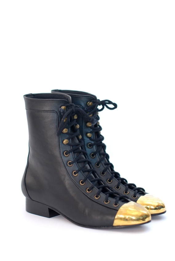 Black leather lace up combat boots with steel cap toes. Brass grommet tops. By Shakuhachi.