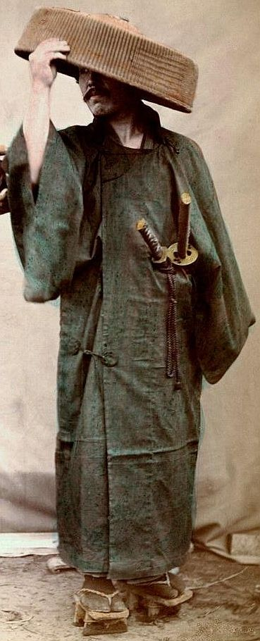 Samurai in foul weather gear; coat and hat. He wears the two swords of the samurai (Katana and Wakasashi) on his left hip.