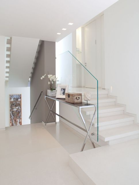 contemporary white entrance hall with taupe feature wall and glass balustrade | Via Home-Trotter