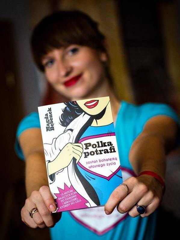 """Magda Bębenek ze swoją pierwszą książką, """"Polka potrafi. Zostań bohaterką własnego życia!"""".  Wyd. Bee the adventure"""