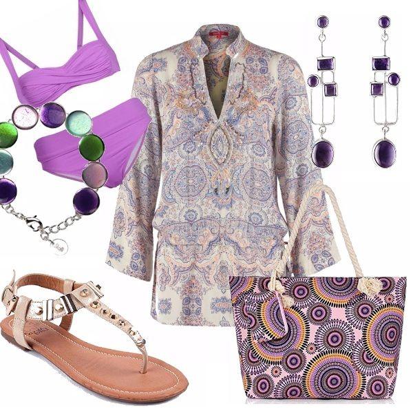Outfit mare settembrino: bikini lilla, abbinato ad una camicia-caffettano a manica lunga con coulisse. Sandalo flat beige con borchiette. Borsa mare in fantasia. Bracciali ed orecchini con pietre dure.