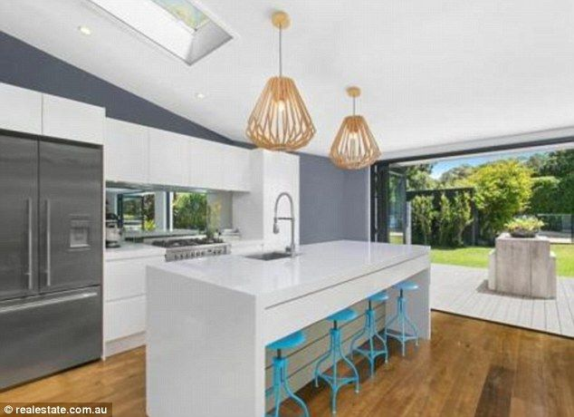 Plenty of room: an open-plan kitchen looks out onto a large backyard complete with entertaining deck with pool