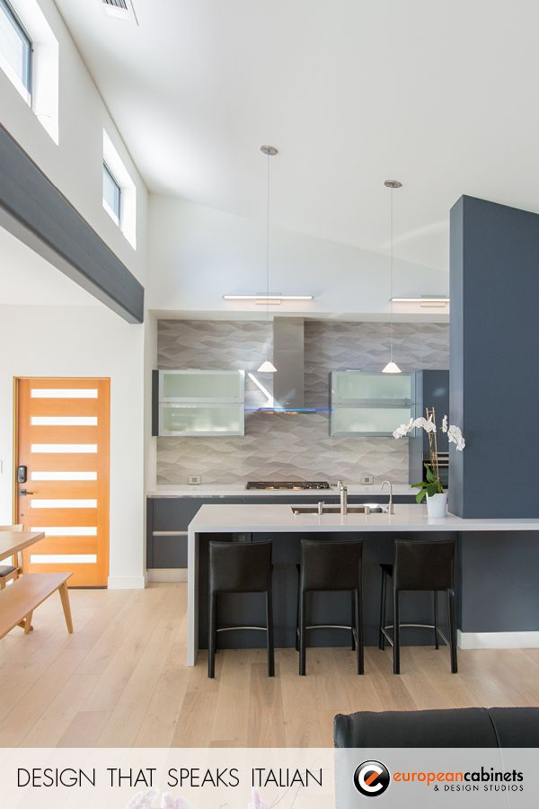 This open, modern kitchen takes advantage of the natural light.   Cabinets from Aran Cucine: Lower cabinets from the Erika collection in Slate Gray; white frosted glass upper cabinets from the Volare collection.  Project in collaboration with architect Tali Hardonag.