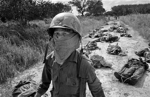 Un camillero vietnamita se cubre el rostro por el hedor de los cadáveres tras un combate en una carretera (1965). (Horst Faas/AP)
