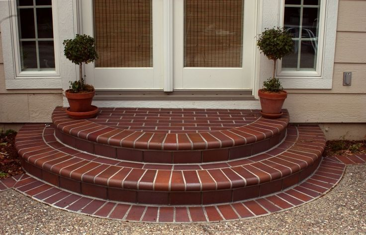 Arched red brick steps on entry way porch landing in running band ...
