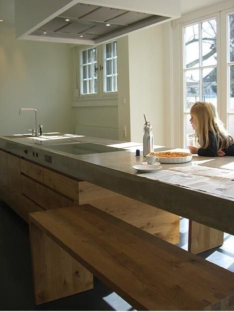 Discovered via Designline Kuche, a concrete and oak kitchen in Germany by Wiedemann Werkstatten, with a few striking details we haven't seen before (cooktop knobs inset into the concrete countertop, modular benches that tuck under a cantilevered dining counter, and double sinks sharing a single faucet).