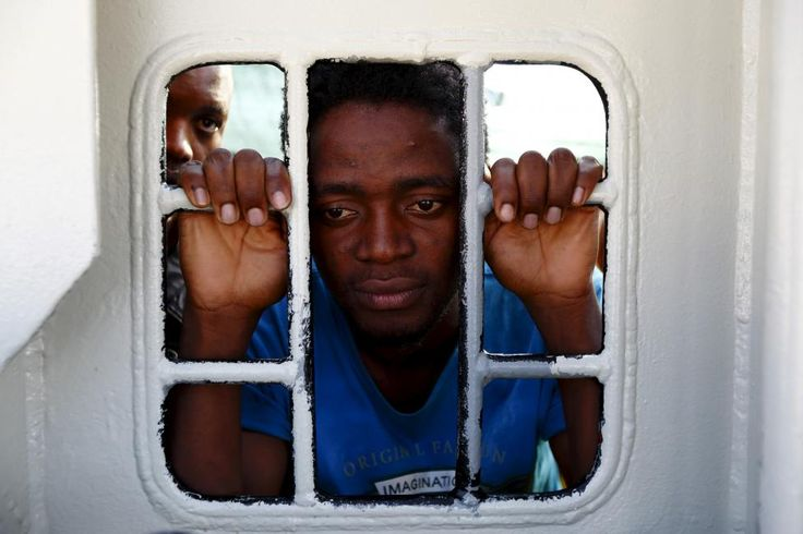 Migrants look out of a window on the Medecins Sans Frontiere (MSF) rescue ship Bourbon Argos as it arrives in Trapani, on the island of Sicily, Italy, August 9, 2015. Some 241 mostly West African migrants on the ship arrived on the Italian island of Sicily on Sunday morning, according to MSF. REUTERS/Darrin Zammit Lupi
