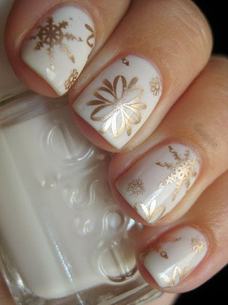 Gold snowflakes over a white top coat makes for the perfect holiday Christmas nail design!