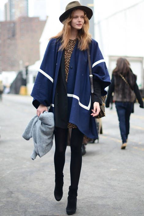 An expert in vintage dressing, model Frida Gustavsson effortlessly pairs a graphic cape with a leopard blouse and men's fedora.   - ELLE.com