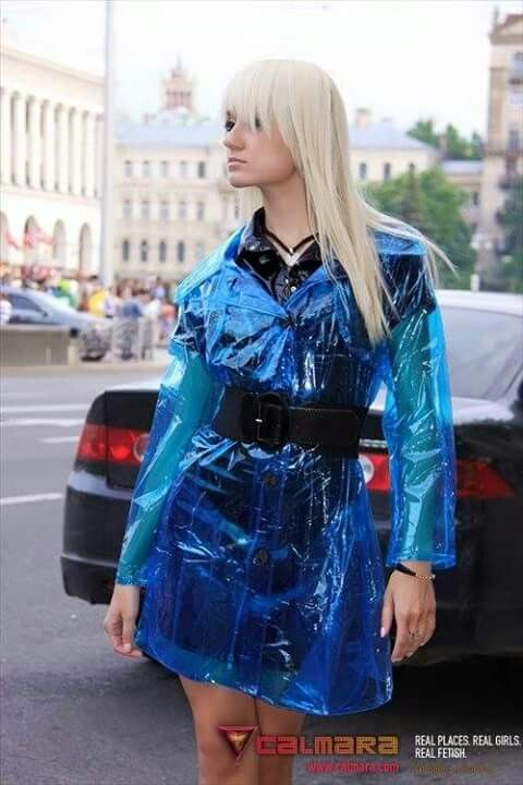 Irina wears a black PVC outfit and a sky blue transparent plastic coat.
