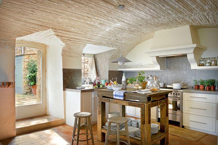 Cocina rústica con techo abovedado, pavimento de toba, encimera de microcemento y mesa tocinera 00380712