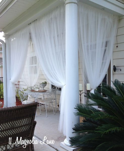 """Inexpensive sheer curtain panels from Ikea (Lill) are used to create a """"screened"""" porch from a covered porch. Read the how-to's at 11 Magnolia Lane."""