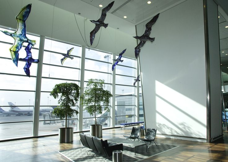 These beautiful birds are flying under the ceiling at gate D2, Pier D. These are created in glass by the Faroese artist Tróndur Patursson in cooperation with the Danish glass master Per Steen Hebsgaard.  The glass has a third dimension because the light shines through and makes the colors vary throughout the day depending on sun's position.