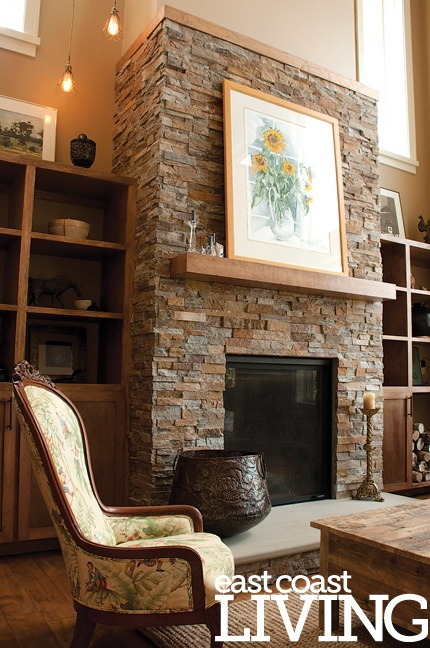 This wood-burning fireplace features the same stone from the home's exterior, bringing the outdoors in. Custom shelves bookend the fireplace. Featured in the Summer 2012 issue of East Coast Living. Photo by Joanna Nickerson, Studio Rouge