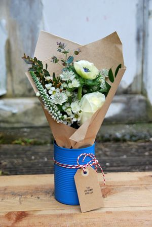 flowers in kraft paper and a painted tin can tied with butcher's twine and brown paper tag. - cute for a hostess gift