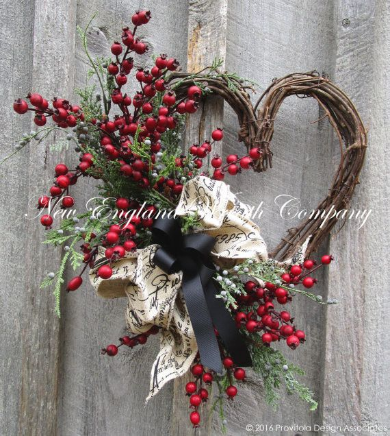 Classic Country French Heart Wreath. An abundance of deep red berry branches and Juniper boughs grace the edge of a rustic grapevine heart. A posh double layer bow in a charming French script print an